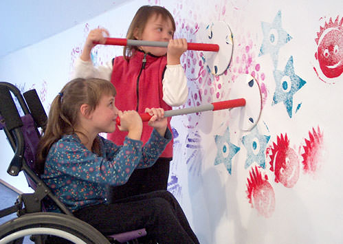 Two elementary school-aged girls are using large stamps to create a design on a large sheet of paper mounted on the wall. The girl on the left is a wheelchair user, the girl on the right is standing. They are both happy and smiling.