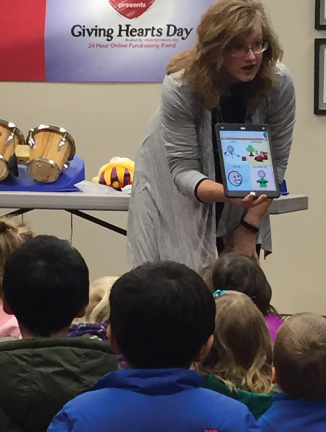 Assistive Technology Consultant Jeannie Krull holds an iPad with a communication app. She is demonstrating how the app works to a group of preschoolers.