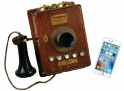 Picture of an old wooden phone and an iPhone.