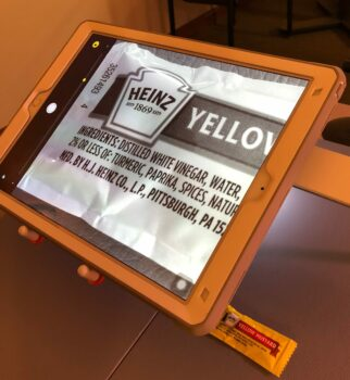 USee stand tablet magnifying a yellow mustard packet