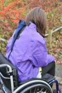 A photo of a woman in a wheelchair with a purple jacket that has velcro securing the back of the jacket.