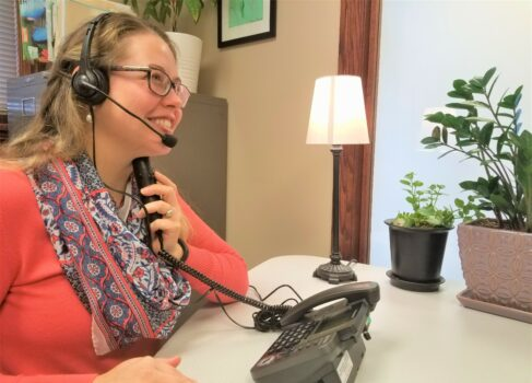 A woman using the TeliTalk Phone with a Headset