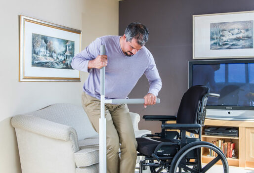 Picture of man moving from rising from the couch using the Advantage Rail. One hand holds the vertical bar of the rail and the other holds the horizontal rail. He is transferring from the couch to the wheelchair.