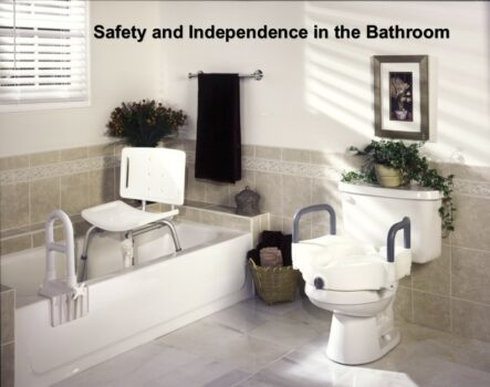 Bathroom with safety adaptations: bathtub with clamp-on tub rail with a shower chair with back in it. Toilet with a raised toilet seat with handles on it.