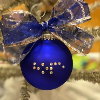 Blue Christmas ball hanging on a tree with crystals spelling out Hope in Braille