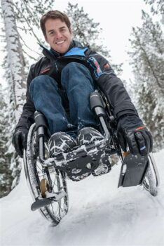Picture of a man using a manual wheelchair with wheelblades installed in an outdoor setting with snow covered ground and evergeens.