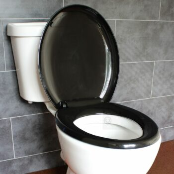 white toilet with black seat and lid. Lid is open.