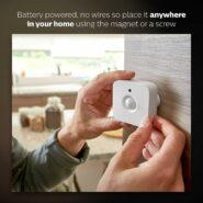 Small white motion sensor mounted to wall