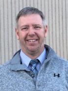 headshot photo of a man wearing a gray sweater