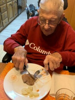 My dad using an adaptive knife and fork to cut meat on his plate at dinner.