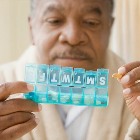 Man holding pill box with a pill in his hand.