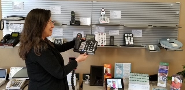 Roxanne is in front of a wall of specialized phones - there are about a dozen of them on a wall and counter display. She's holding a phone and looking at it. The phone is black with large buttons and a text display.
