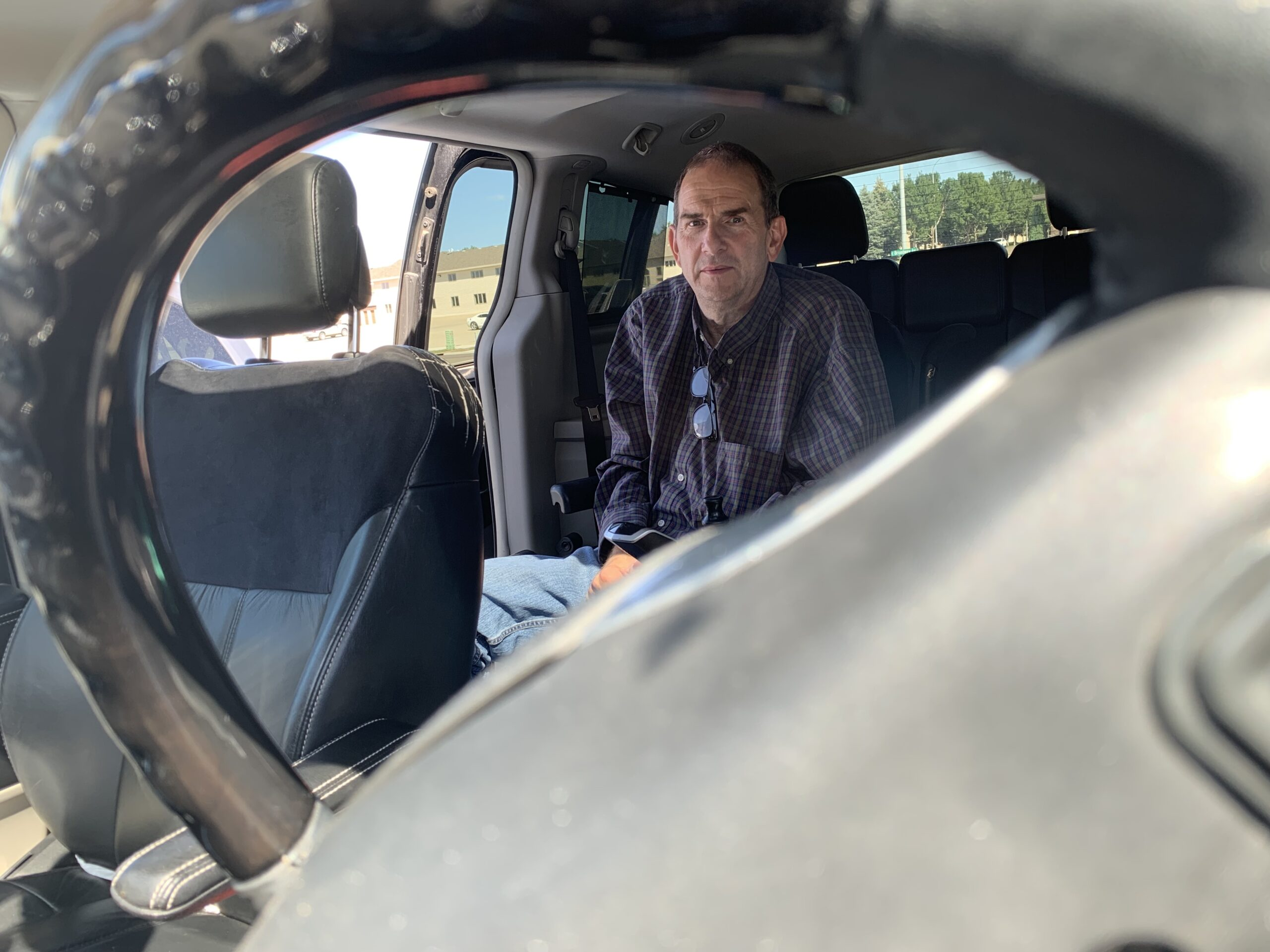 Royce inside his van. The photograph is taken through the steering wheel. He is in the back of the van where he will begin to transfer to the diver's seat.